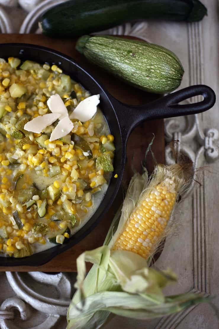 Calabacitas con Elote (Zucchini with Corn) in a cast iron skillet with fresh corn and zucchini
