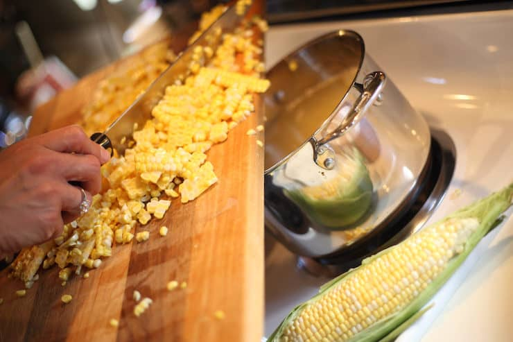 shucked corn going in to pot to boil