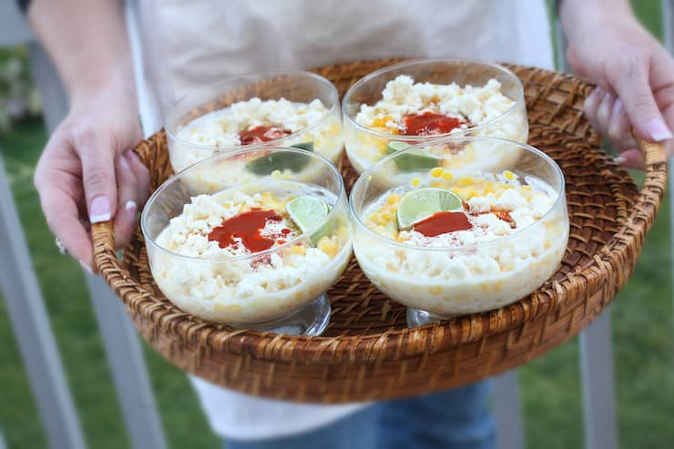 holding a tray with four cups of Mexican street corn in cups