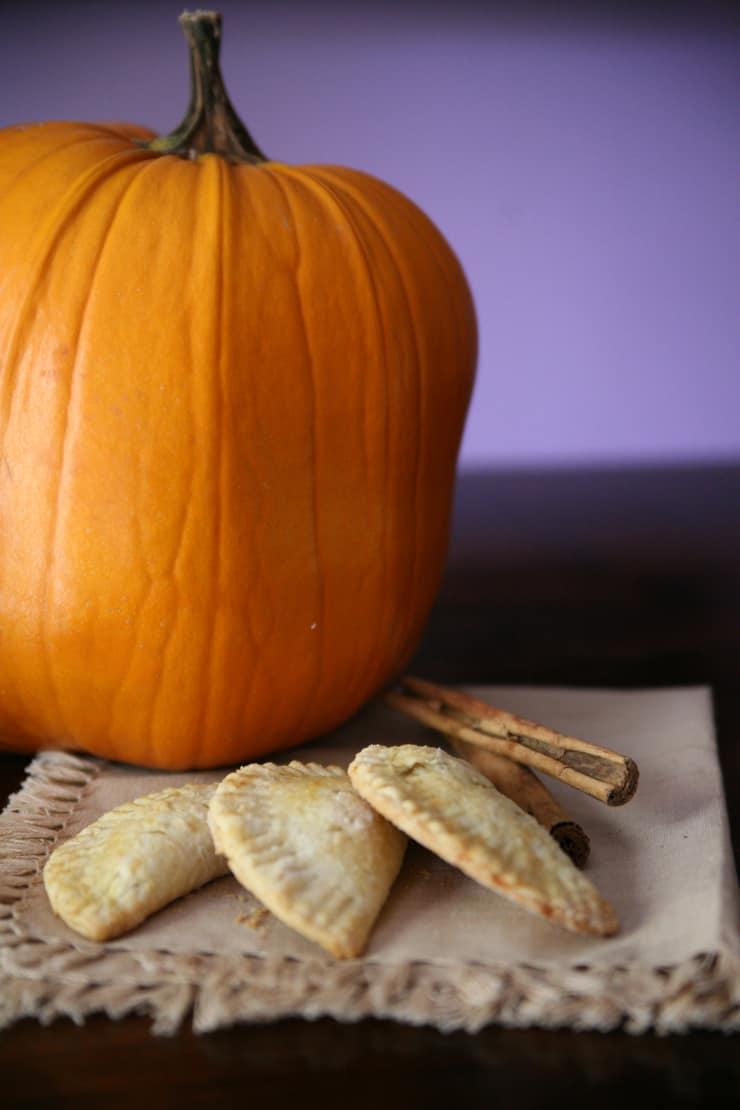 pumpkin empanadas and cinnamon sticks with an orange pumpkin