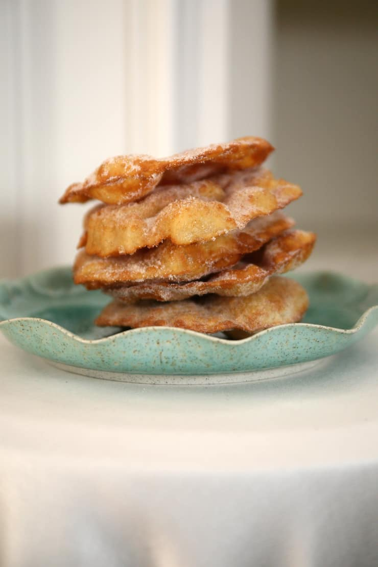 bunuelos sweet Mexican fritters piled high on a ceramic light teal plate