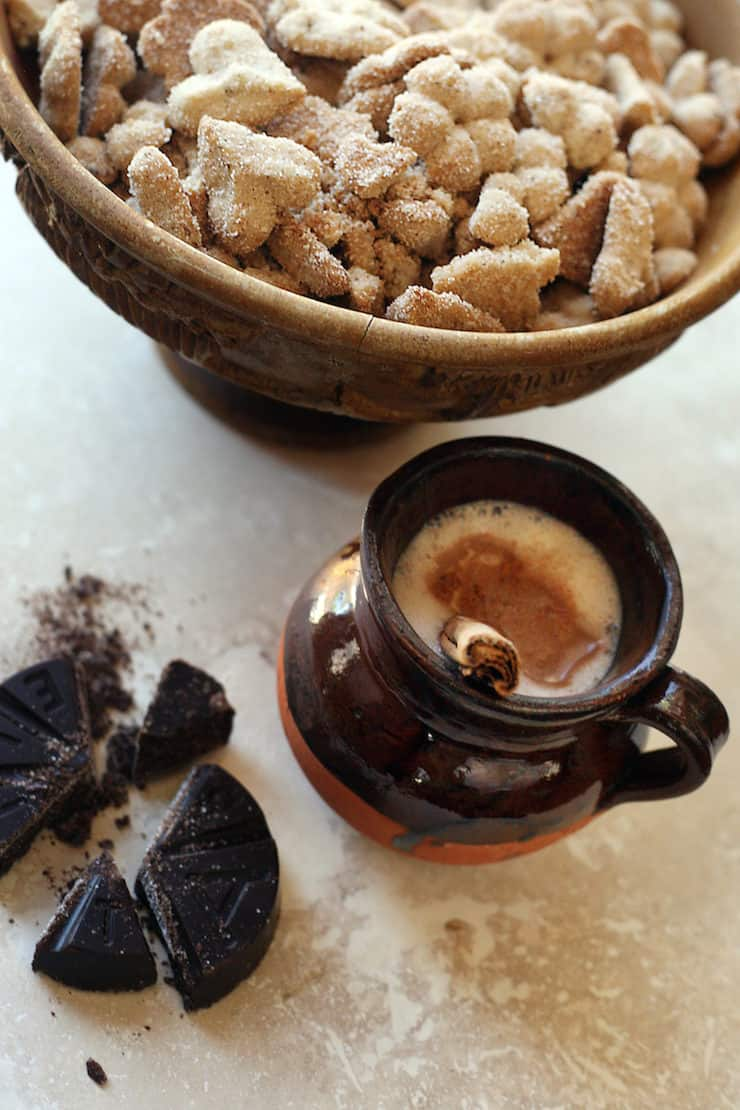 biscochos (Mexican wedding cookies) in a wooden bowl with a side of Mexican hot chocolate