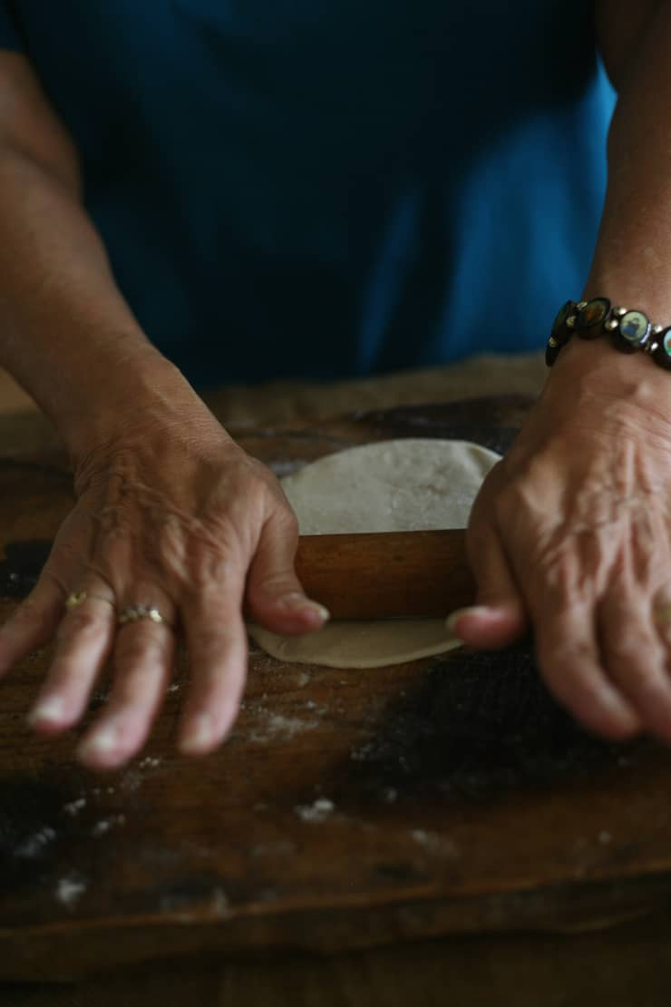 mother grandma hands rolling dough with a rolling pin to make a flour tortillas