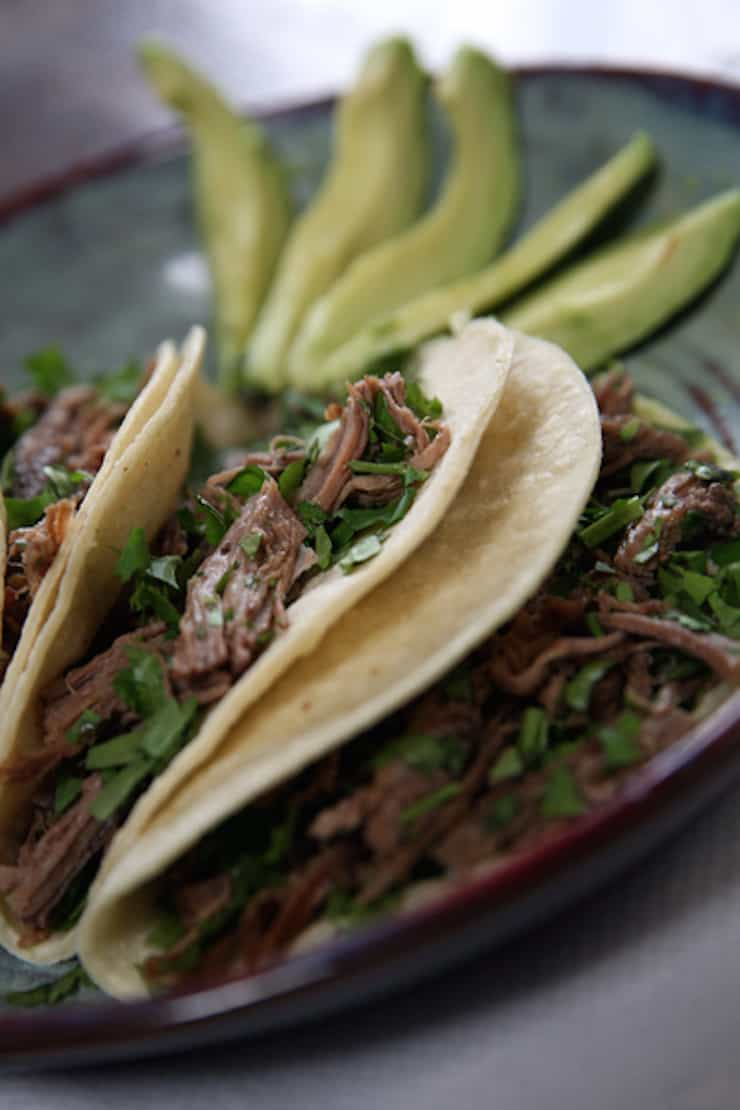 closeup of Beef Brisket Tacos with slices of avocados