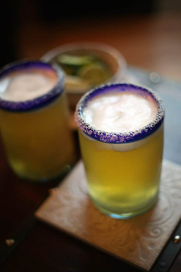 two chilled glasses filled with beer and lime rimmed with salt chelada