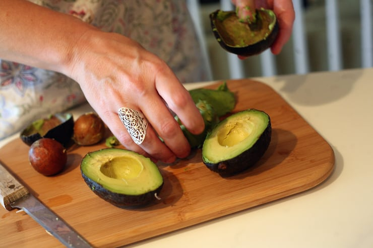 hands holding avocados making homemade classic guacamole