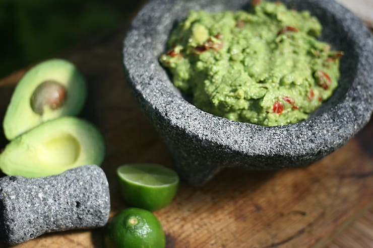 molcajete lava stone filled with guacamole and limes on the side