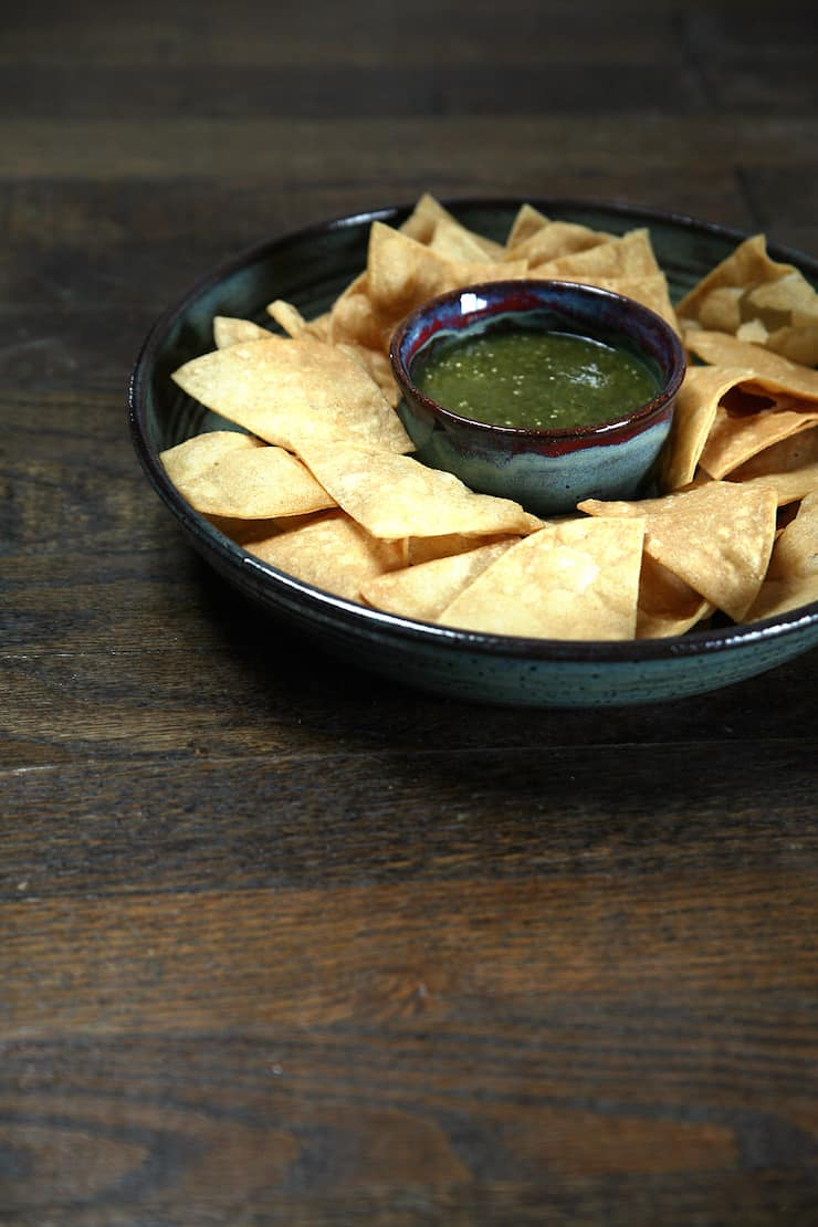 easy salsa verde recipe -- salsa verde in a chip bowl surrounded with tortilla chips