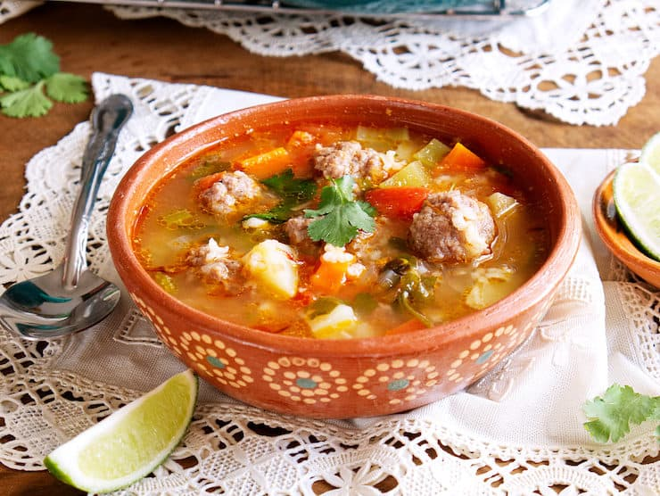 Mexican pottery bowl with caldo de albondigas served with a lime wedge on a doily