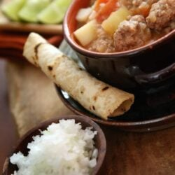caldo de albondigas soup with a rolled corn tortilla and minced onions