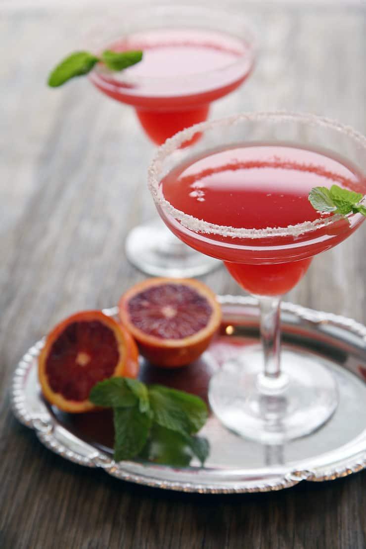 two Blood Orange Mezcal Margaritas with a salt rim