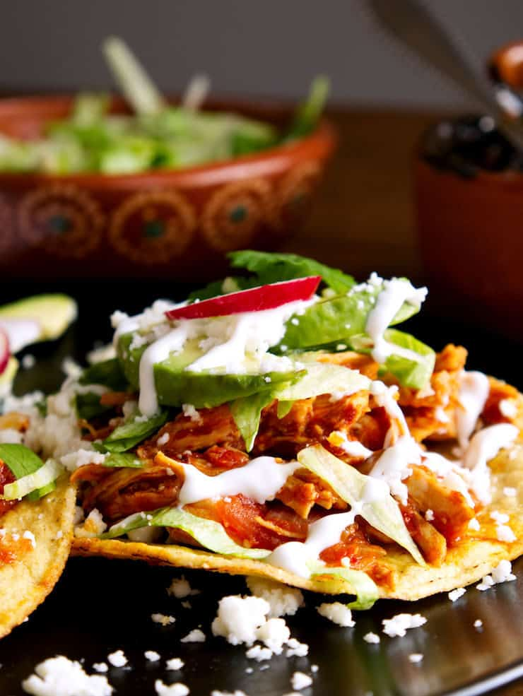 close up of tostada topped with spicy and smoky chicken Tinga