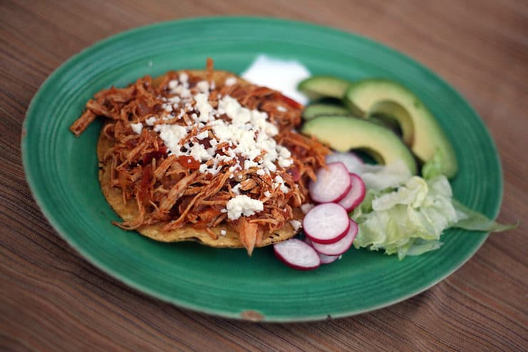 green plate with a chicken tinga tostada and a side of avocado slices lettuce and crema