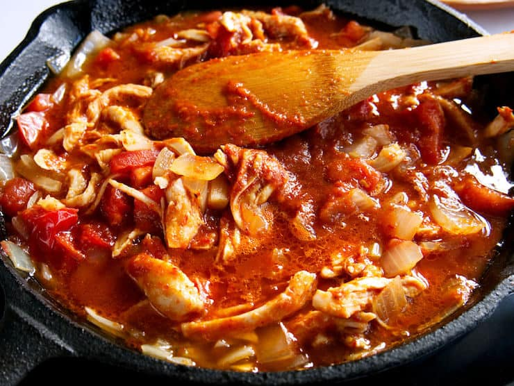 cast iron with chicken Tinga cooking and a wooden spoon