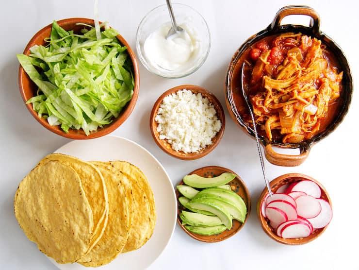 tostada bar of ingredients to make chicken Tinga tostadas