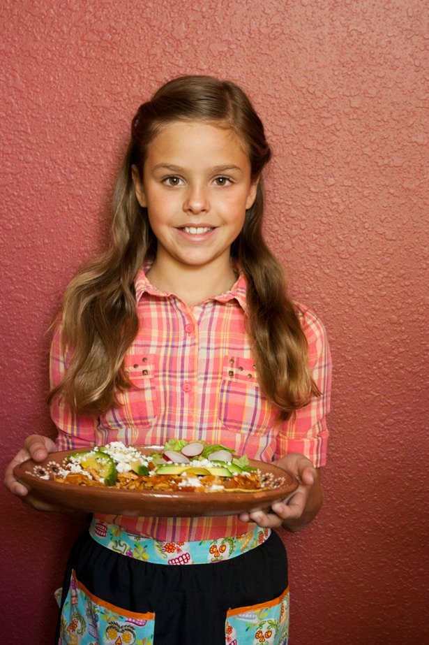 girl holding a Mexican platter of tostadas filled with chicken Tinga