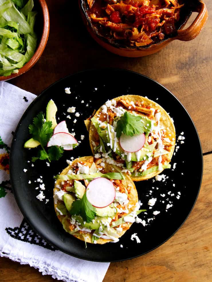 black plater with two tostadas loaded with shredded chicken Tinga lettuce avocado and queso fresco