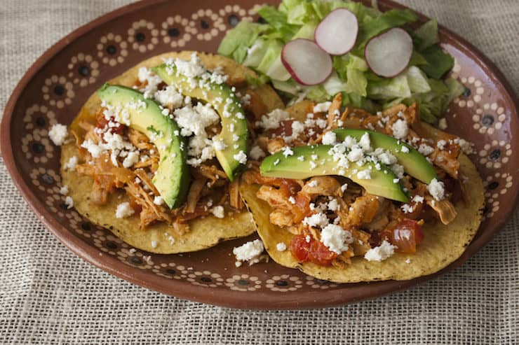 Mexican platter with two tostadas filled with shredded spicy chicken Tinga garnished with avocado slices and queso fresco