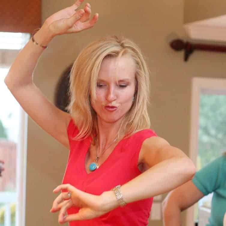A woman in a red shirt dancing zumba