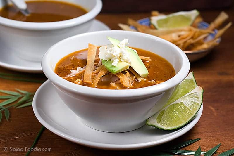 A bowl of chicken tortilla soup served on a white plate