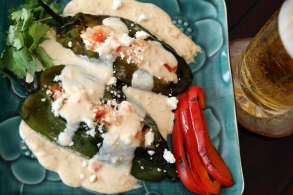 chile relleno camarones poblanos shrimp on a teal plate with a cold beer on the side