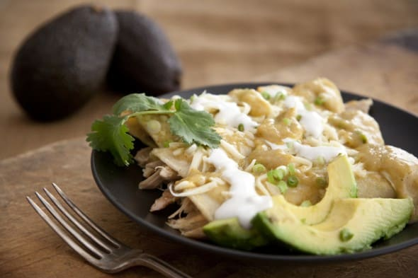 Enchiladas Verdes (Green Enchiladas) rolled on a black plate drizzled with Crema sour cream