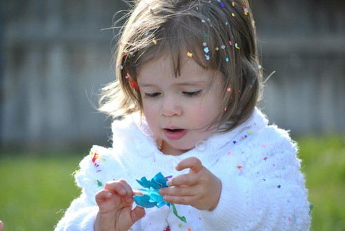easter little girl with a cracked cascaron on her head and confetti on her white sweater