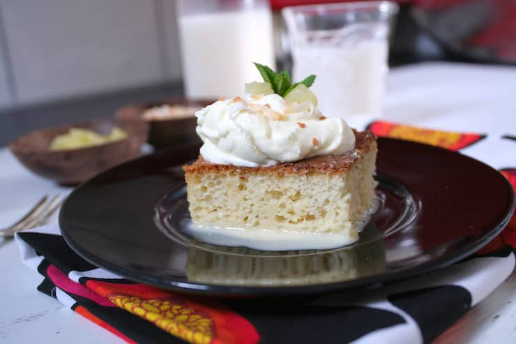 slice of tres leches cake with a dollop of whipped cream