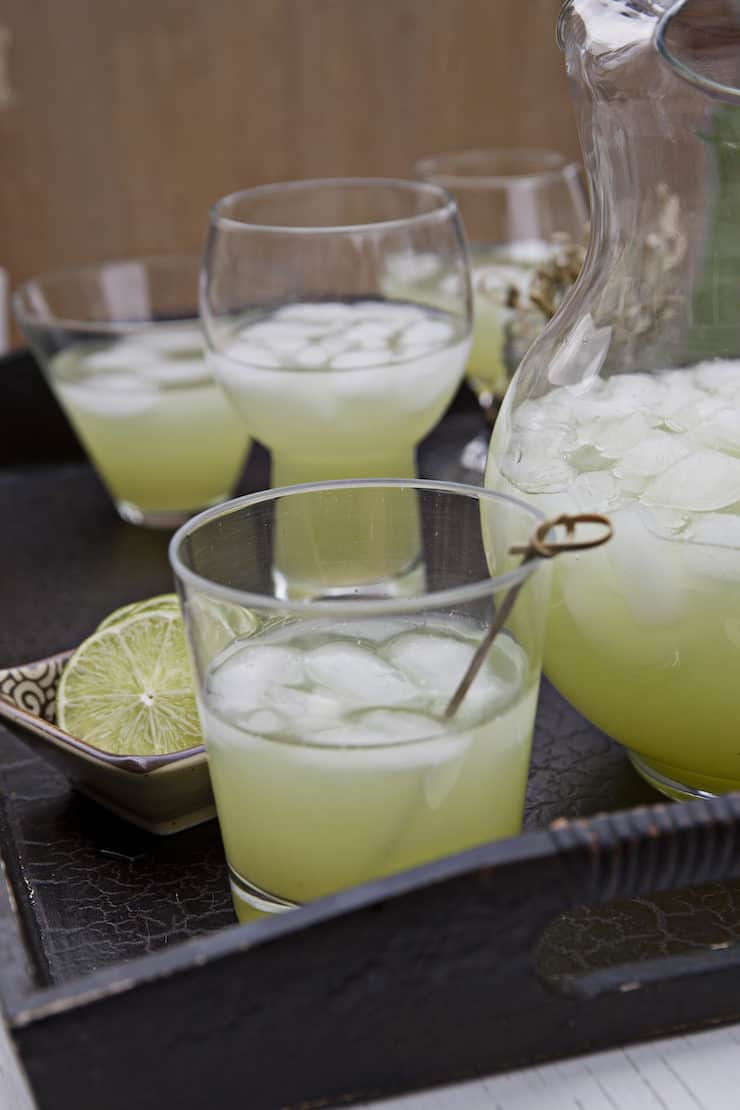 glasses and pitcher in a brown tray filled with agua de pepino cucumber lime water