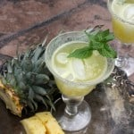 Agua de Piña or Pineapple Cooler ready and served in two impressive glasses with pieces of pineapple right next to them