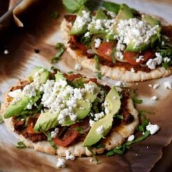 Huaraches Topped with Chorizo Refried Beans, Tomatoes and Avocados