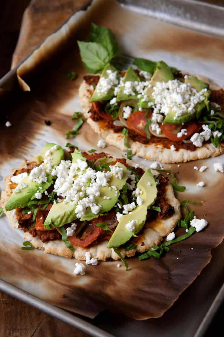 Huaraches Topped with Chorizo Refried Beans, Tomatoes, and Avocados