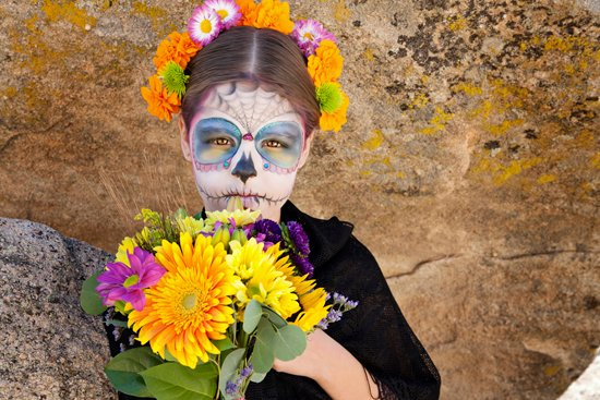 girl wearing day of the dead makeup holding flowers