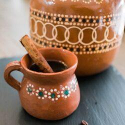 cafe de olla in an earthenware mug with a cinnamon stick garnish