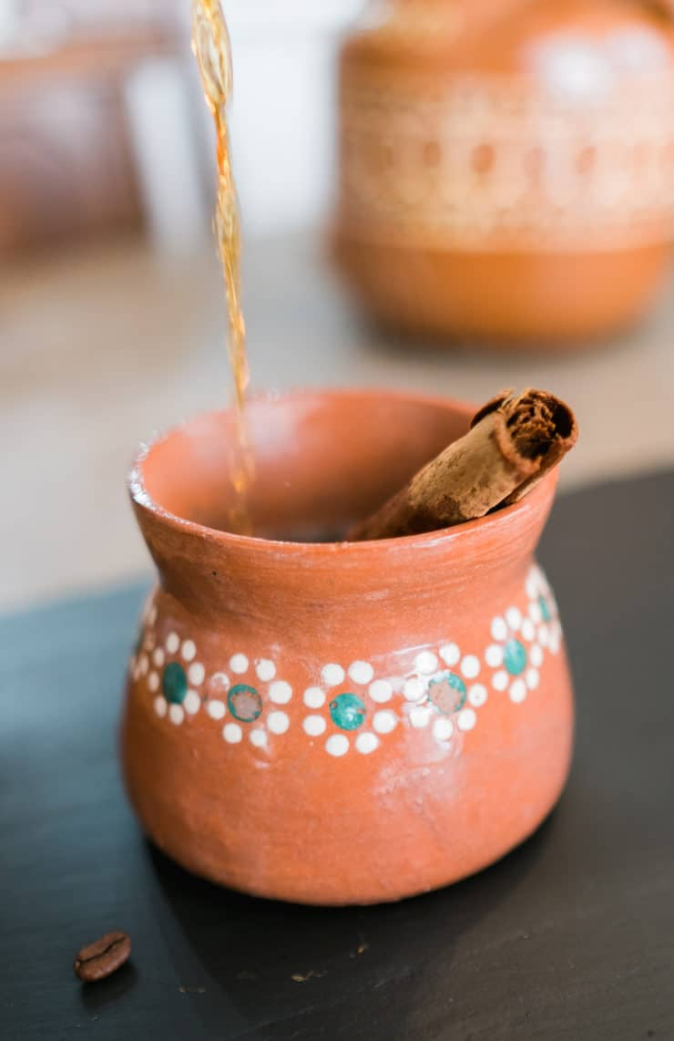 pouring cafe de olla in a Mexican clay pottery cup