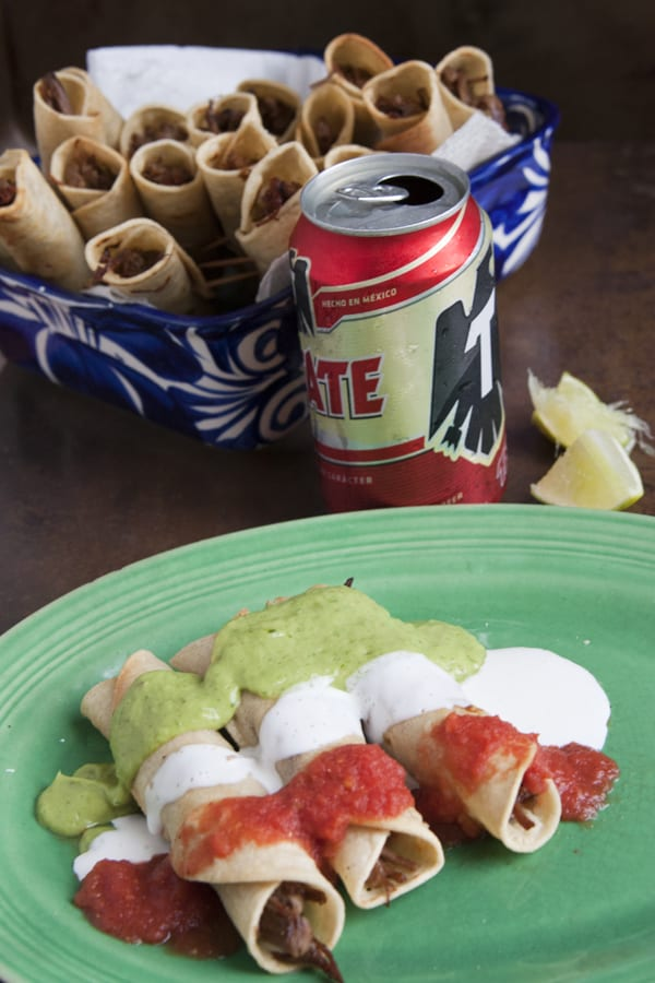 three falutas filled with shredded beef on a green plate drizzled with salsa Crema avocado salsa banderas taquitos with a Tecate in the background