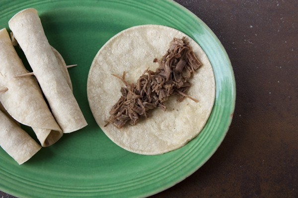 filling corn tortillas with shredded brisket flautas