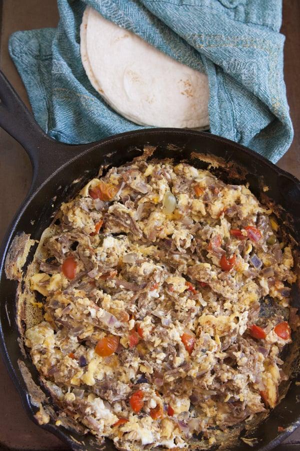 machaca con huevo MACHACADO con huevo in an iron skillet with a stack of flour tortillas on the side