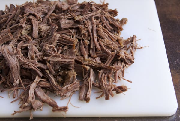 slow cooked shredded beef brisket on a cutting board