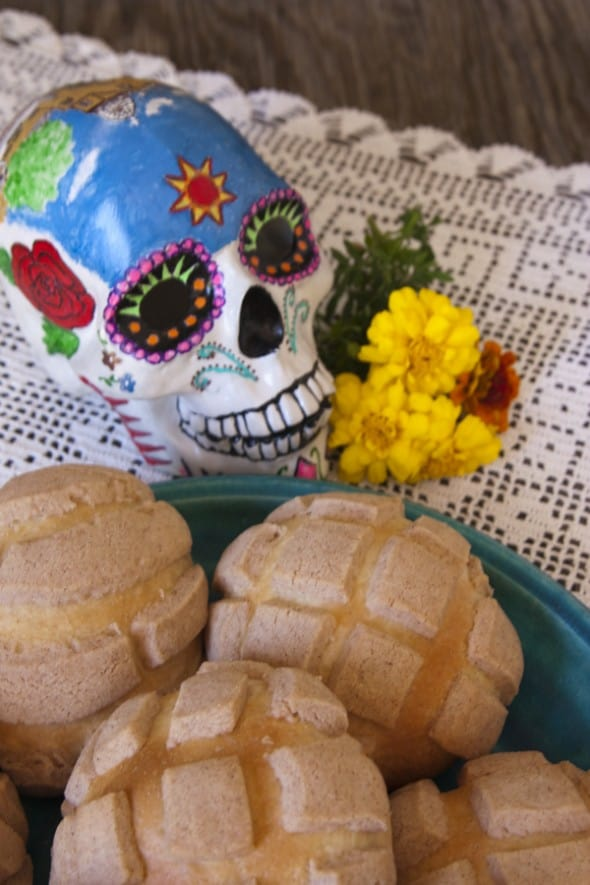 plate of Mexican sweet bread conches with a sugar skull and marigolds