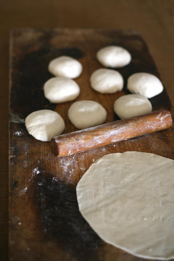 One tortilla, a small wooden rolling pin and eight testales bolts balls of dough on a wooden board
