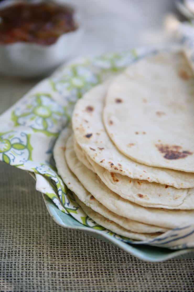 A stack of Homemade Flour Tortillas on a plate lined with a cloth