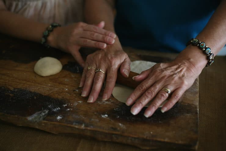 Mother and daughter hands making homemade flour tortillas with a small wooden rolling pin