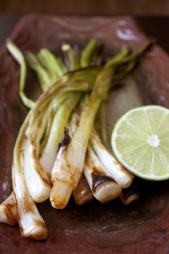 A platter of Cebollitas Asadas (grilled green onions) with a lime on top