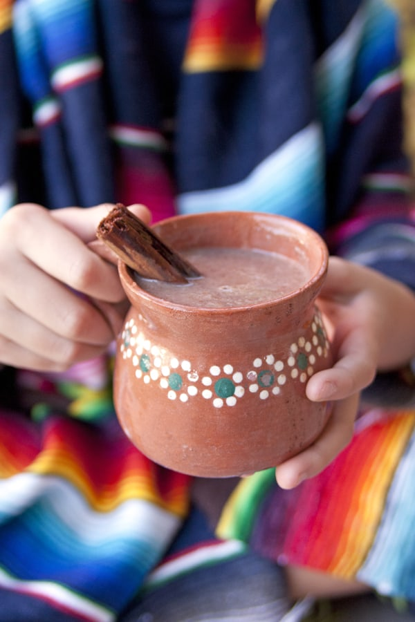 Mexican Hot Chocolate Abuelita held in girls hands covered in a serape