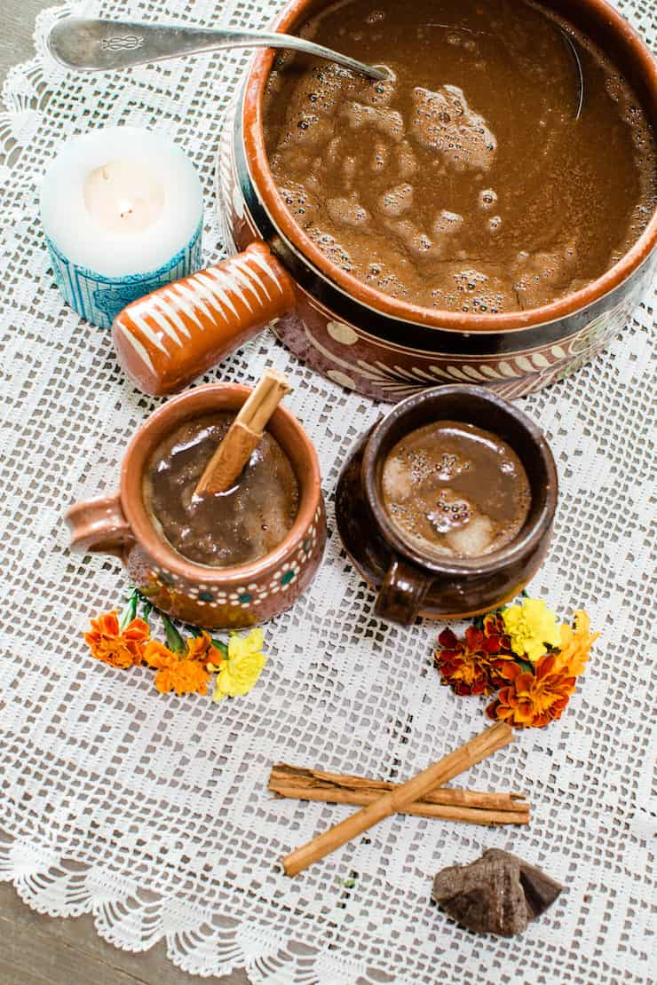 Mexican Hot Chocolate in a vintage barre Mexican pottery with two cups on a doily marigolds and cinnamon sticks
