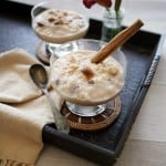mexican rice pudding, known as arroz con leche, in short coupe glasses and garnished with cinnamon on a black serving tray