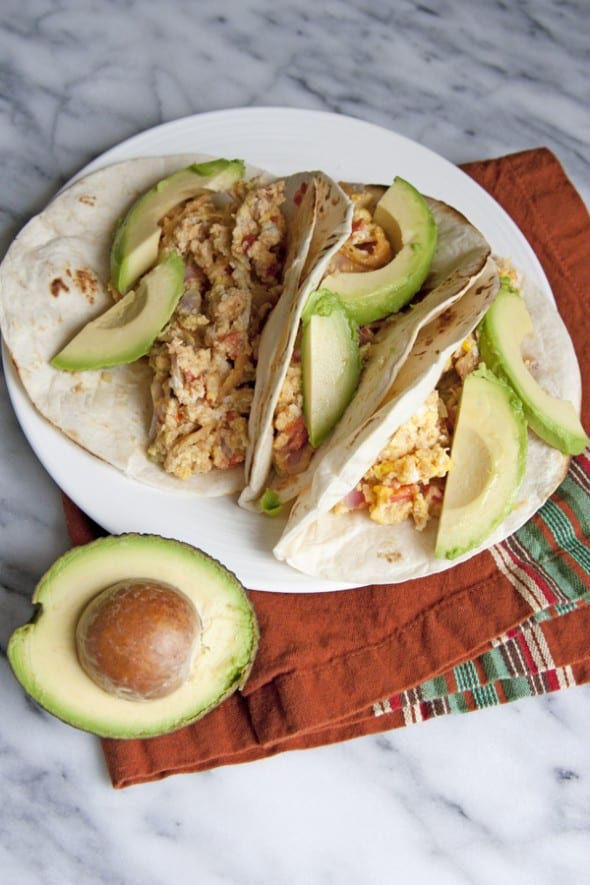 breakfast Migas tacos on a white place with slices of avocado