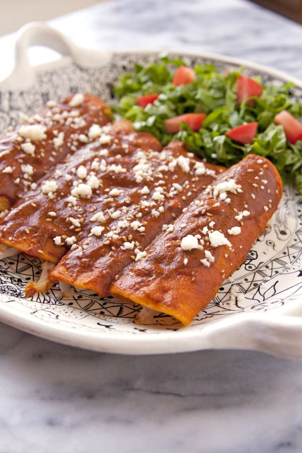 chicken mole enchiladas on a Mexican black and white platter with a side salad