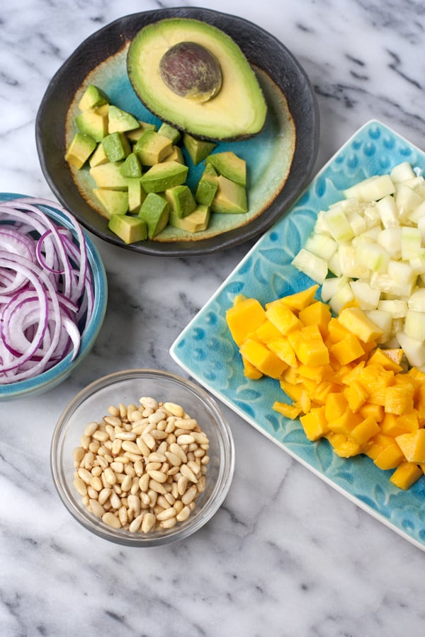 avocado mango cucumber and red onions prepped for salad